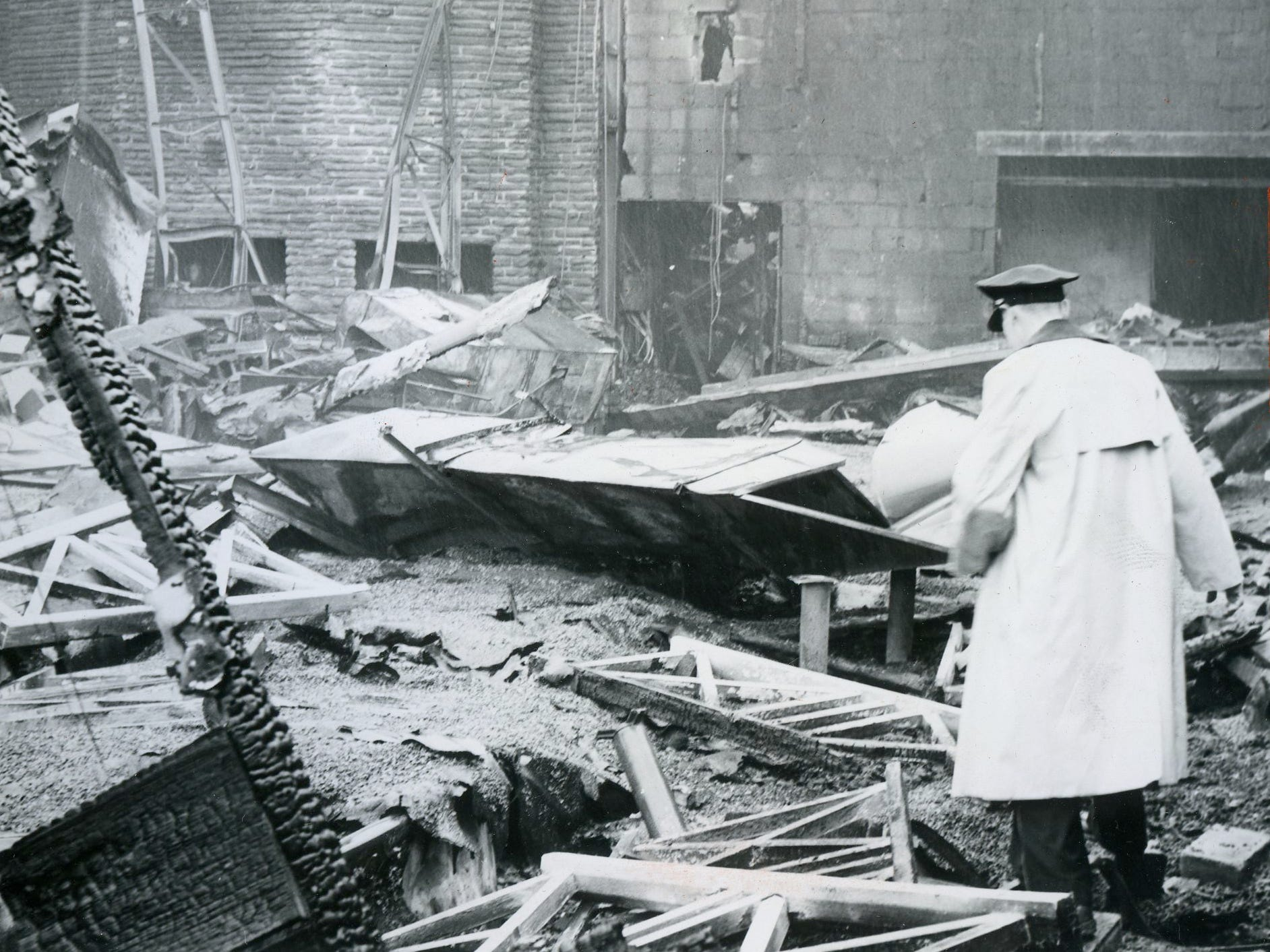 Charcoal ovens are seen in the background as a fire official surveys the aftermath of a fire that destroyed the original building of The Pub in Pennsauken in 1962. The Pub was later rebuilt on the same site.