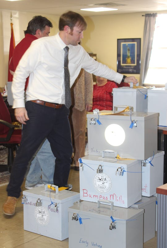 Stewart County Administrator of Elections Daniel Perigo stacks the locked ballot boxes at the election commission meeting March 26, 2019.