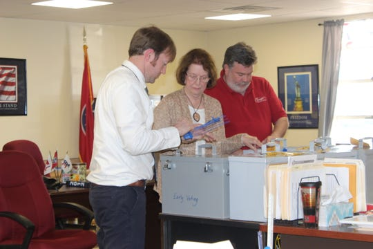 Stewart County elections officials, including Administrator Daniel Perigo, left, Commissioner Nellie Settle and acting Chairman Kyle Mallory, lock the ballot boxes after getting the go-ahead from state officials, despite their absence of a quorum at their March 26, 2019, meeting.