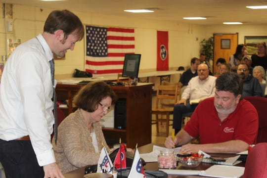 The final two members of the Stewart County Election Commission, Nellie Settle and Kyle Mallory, sign paperwork after their March 26 meeting as Elections Administrator Daniel Perigo and a full gallery of onlookers watch. The commission has had three unexpected resignations in the past few weeks after allegations of outside influences.