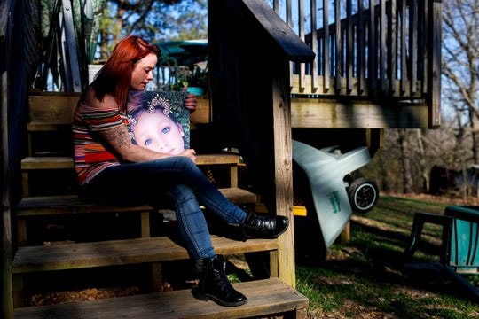 Lacie Sloan, a Clarksville resident, clutches in her arms an enlarged version of the most recent photo she has of her daughter Natalie Lyle, who died by suicide in March.