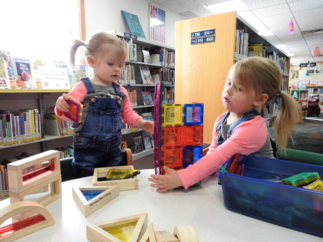 Sisters Grace and Harper Smith play with blocks in the children's room of the Coshocton Public Library on Wednesday.
