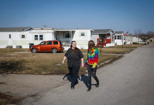 Janet Hooks walks along Collins Drive with her daughter, Rebekah Wiles, 16, on Tuesday, March 26, 2019, at Midwest Country Estates in Waukee. A new company has purchased the mobile home park and advised residents there of its intention to raise monthly rents by $205.
