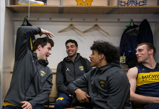 Michigan players include forward C.J. Baird (24), guard Eli Brooks (55) and forward Austin Davis (51) share a laughter in the locker room before practice at the Honda Center in Anaheim, Calif., Wednesday, March 27, 2019.