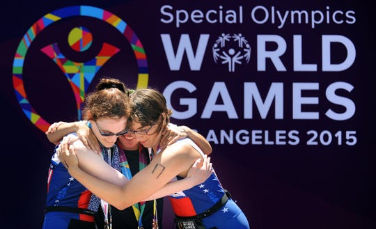 Medal winners Amy Noctor, left, and Courtney Dreyfus, right hug gold medal winner Florencia Barranque after the triathlon competition of the Special Olympics in 2015 in Long Beach, Calif.