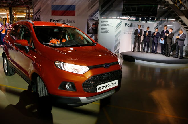 In this photo taken on Tuesday, Dec. 2, 2014, Russian Prime Minister Dmitry Medvedev, second right, attends the launch of Ford EcoSport production during a visit to Ford Sollers at a plant in Naberezhnye Chelny, in the Russia's region of Tatarstan, about 450 miles east of Moscow, Russia. Ford said Wednesday March 27, 2019, that it will close three factories in Russia, causing heavy job losses, as it closes this vehicle assembly plants in Naberezhnye Chelny and pulls out of passenger vehicle manufacturing in the country. (Dmitry Astakhov, Sputnik, Government Pool Photo via AP)