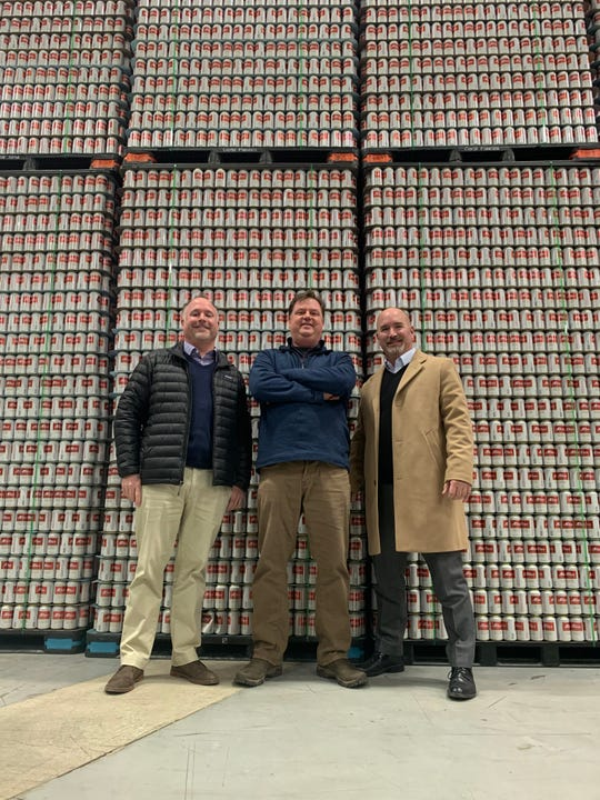( From left) Pat Kruse, Eric Stief and Carl Erickson, co-founders of Detroit National Brewing Company, stand in front of cans of Altes Original Detroit Lager. The three men relaunched Altes 20-plus years after it discontinued.