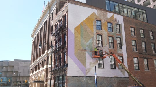 On the east-facing side of the Detroit Foundation Hotel at 234 W. Larned, artists Hubert Massey, 60, and Henry Heading, 61, are bringing back to life the work of a legendary Detroit artist over three decades their senior -- 94-year-old Charles McGee.
