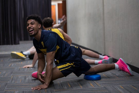 Michigan guard David DeJulius shares a laughter with teammates guard Adrien Nunez and forward Colin Castleton as they warm up in the hallway before practice at the Honda Center in Anaheim, Calif., Wednesday, March 27, 2019.
