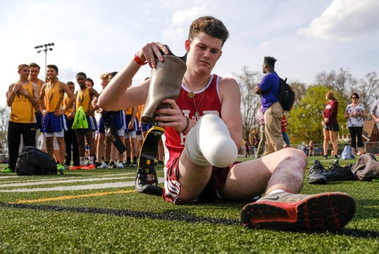 University of Detroit Jesuit High School and Academy runner Sean English prepares his prosthetic to run with before his first and last high school race on Wednesday May 2, 2018 at the school in Detroit. English lost his leg while stopping to help six car accident victims.