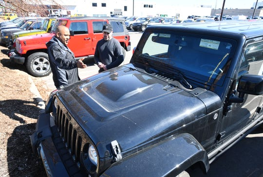 Sales consultant Sean Walker, left, shows Jeeps to Andrej Petrovski at the dealership, Southfield Chrysler Certified Pre-Owned.