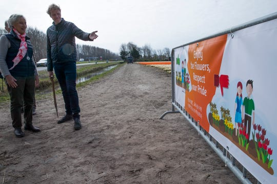 """Simon Pennings gestures as he explains one of the new banners, with the text in English and Chinese reading """"Enjoy the flowers, respect our pride"""" , at the entrance to one of his flower bulb fields in Noorwijkerhout, near Lisse, Netherlands, Wednesday, March 27, 2019."""