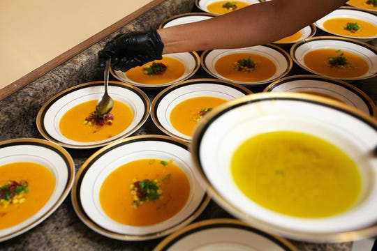 Chef Anicia Peden drizzles cannabis oil over sweet potato chowder at a members only dinner hosted by A Table For Twenty at a private home in Humboldt Park. (Kristan Lieb/Chicago Tribune/TNS)