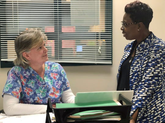 In this Feb. 28, 2019 photo, Linda Espinosa, left, a school nurse at Freedom Middle School in the Atlanta metro-area, speaks to school counselor, Tijuana Williams, about schoolgirls coming in to her office to get sanitary pads, in Atlanta.