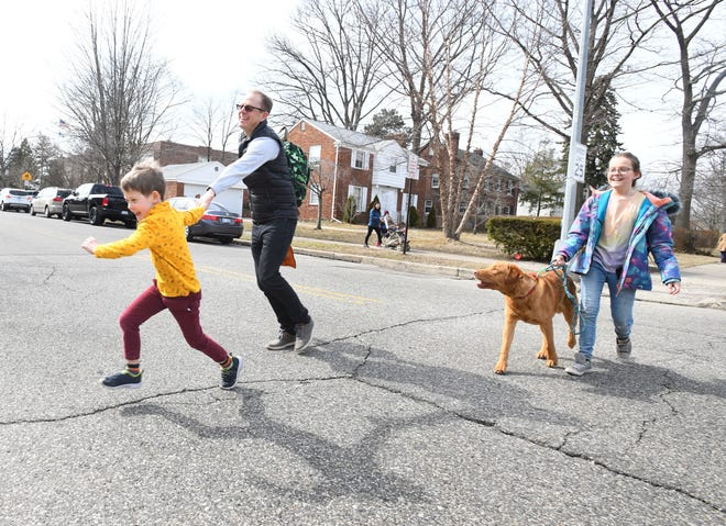 Kindergartener Johnny Martin, 6, leads his dad John Martin along with his fifth grader sister Elena Martin, 11, and family dog Westley on their walk home from Defer Elementary School in Grosse Pointe Park.