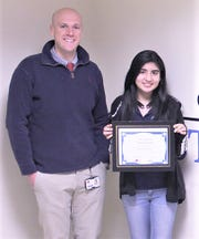 STEM Academy Principal Rob Sherburne presents a student of the month certificate to Karen Quintanilla.