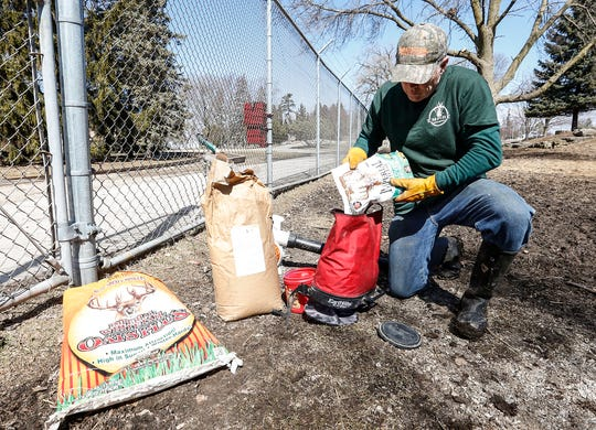 Todd Shippee of Empire Land Management fills his seed spreader with clover seed Friday, March 22, 2019 in the deer pen at Lakeside Park in Fond du Lac.