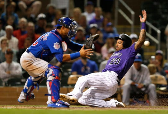 Ian Desmond, shown sliding into home plate to score a run in an exhibition game Saturday in Arizona against the Chicago Cubs, and the Colorado Rockies open their season Thursday with a 2:10 p.m. game at Miami.