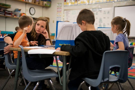 Kindergarten teacher Megan Back helps her student Drexler Martin, left, find the words for his how-to book while classmates Leo Hathaway, center, and Raelin Dekrey, right, work on their books before recess on Wednesday, March 27, 2019, at Riffenburgh Elementary School in Fort Collins, Colo.