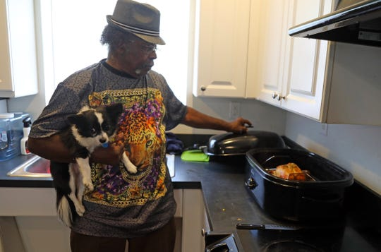 Eddie Clemons prepares to baste a roast chicken for supper at his home in Fort Myers in a kitchen adapted for his physical needs.