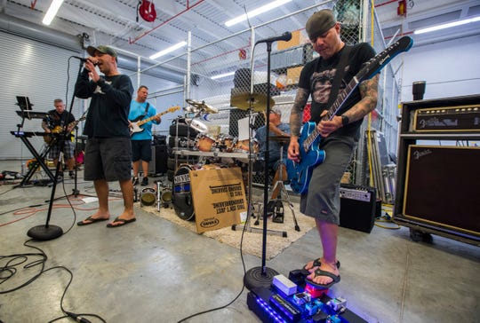 Members of the band Signal III rehearse Tuesday evening at the Cape Coral Police Department's headquarters. The Band members include: Tom Eberhardt, guitar; John Howes, bass; Walt Herman, vocals; Chad Hartzell, guitar; Mick Jahaaski, drums; Steve Barnes, guitar; and Gabrielle Fernandez, vocals. All band members are local law enforcement officers.