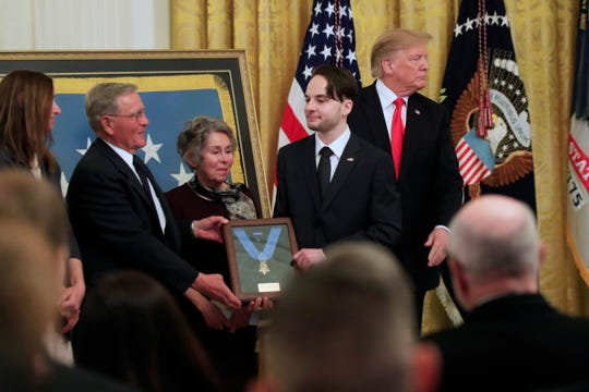 President Donald Trump awards the Medal of Honor to Army Staff Sgt. Travis Atkins and joins Atkin's son Trevor Oliver, right, and his parents John and Elaine Atkins of Bozeman, Mont., after accepting the posthumous recognition for conspicuous gallantry in Iraq in June 2007, in the East Room of the White House, Wednesday March 27, 2019, in Washington.  (AP Photo/Manuel Balce Ceneta)