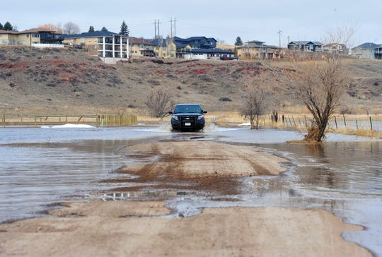 A Cascade County Sheriff's Office vehicle crosses a flooded section of road in Gibson Flats Wednesday.