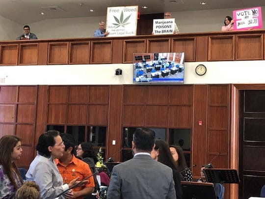Senators confer during a brief session break Wednesday morning, as pro- and anti-recreational marijuana legalization bill hold signs.