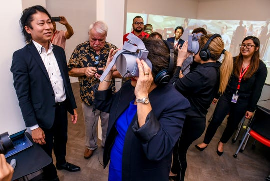 Gov. Lou Leon Guerrero, front, and M80 Systems' Assistant General Manager Jessica Leon Guerrero, experience the view of a 360-degree virtual undersea environment through the use of 3-D goggles during a tour of the 5G Open Partner Program Lab at the Docomo Pacific headquarters in Tamuning on Wednesday, March 27, 2019.