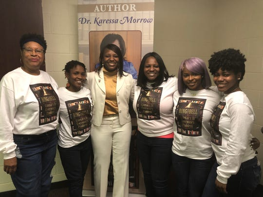 """Dr. Karessa Morrow is surrounded by family members wearing shirts with the name of Morrow's book """"Ring the Bell: Literacy is Everyone's Problem."""" Pictured, from left, are Nellie Weddle, Morrow's aunt from Washington, D.C.; her niece Aliyah Phillips; her sister Deborah Phillips; and her nieces Cayley Phillips and Brooklyn Phillips."""