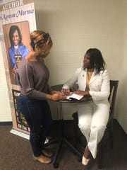 """Dr. Karessa Morrow, a Jackson native, talks to Lynn Bond before signing her book """"Ring the Bell: Literacy is Everyone's Problem"""" during Morrow's book release party Saturday."""