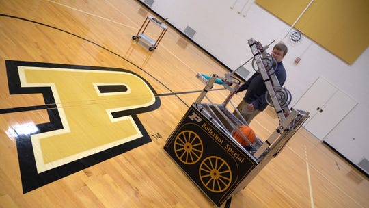 Michael Linnes, the robotic team's faculty advisor, helps test the BoilerBot Special at the co-rec.