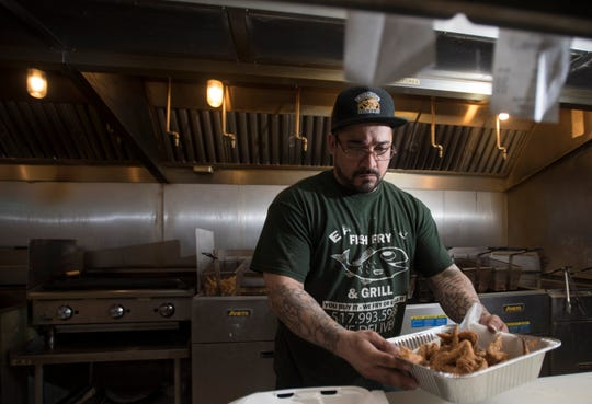 Juan Turrubiates pulls an order of Eastside Fish Fry & Grill's popular seasoned fried chicken wings. Turrubiates spent eight years in prison before he became one of the restaurant's managers five years ago.