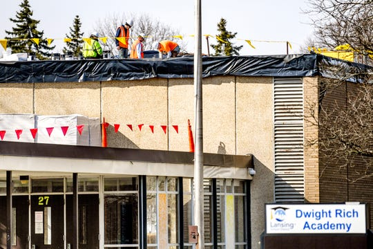 A crew works on the roof at Dwight Rich Academy on Wednesday, March 27, 2019, in Lansing.