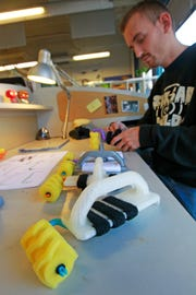 Jesse Goudreau works on the device he created for students at Manitoba Elementary and Middle School who have difficulties gripping a paint brush.