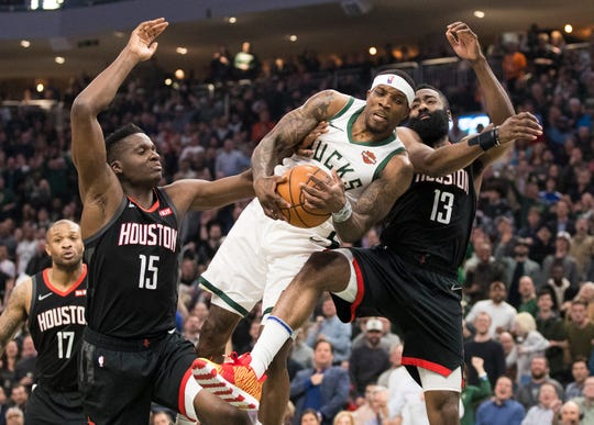 Bucks guard Eric Bledsoe  grabs a rebound between Rockets center Clint Capela (15) and guard James Harden.