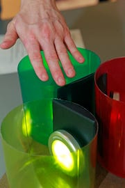"""A student demonstrates the """"Engagement Bucket"""" that was created by Maria Sisul for a Manitoba Elementary and Middle School student who is deaf. The device that lights up is sensor activated. It also helps students sort items."""