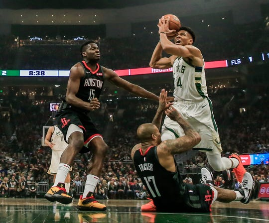 Giannis Antetokounmpo drives over Houston Rockets forward PJ Tucker and past center Clint Capela on Tuesday night.