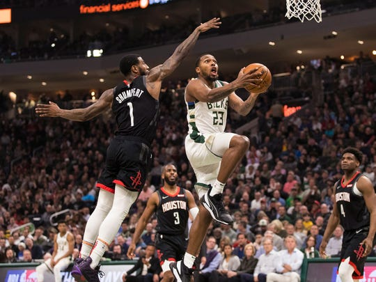 Bucks guard Sterling Brown gets past  Rockets guard Iman Shumpert.