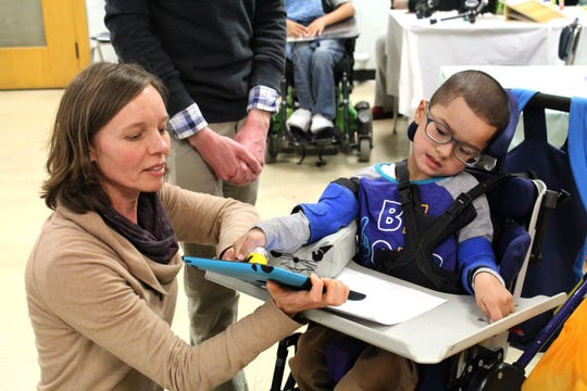 J.J. Guzman, a student at Milwaukee Public Schools' Manitoba Elementary and Middle School, tries the new stylus designed by Jason Ward. The stylus has a special grip so J.J. can hold it in his hand and use an iPad. Michelle Milbauer, occupational therapist at Manitoba, helps him.