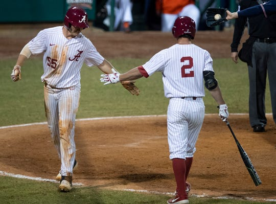 Alabama's Drew Williamson (55) and Alabama's John Trousdale (2) celebrate Williamson's go ahead run in the eighth inning against Auburn at the MAX Capital City Classic at Riverwalk Stadium in Montgomery, Ala., on Tuesday March 26, 2019.