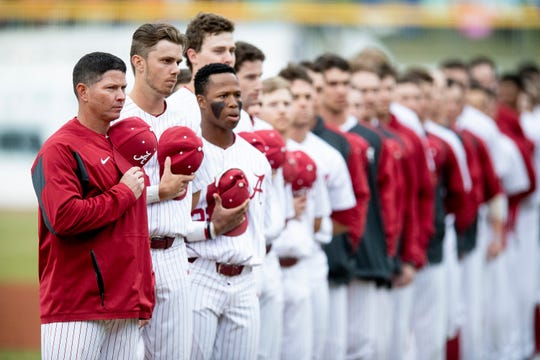 Alabama head baseball coach Brad Bohannon and his team stand during the National Anthem before the MAX Capital City Classic at Riverwalk Stadium in Montgomery, Ala., on Tuesday March 26, 2019.