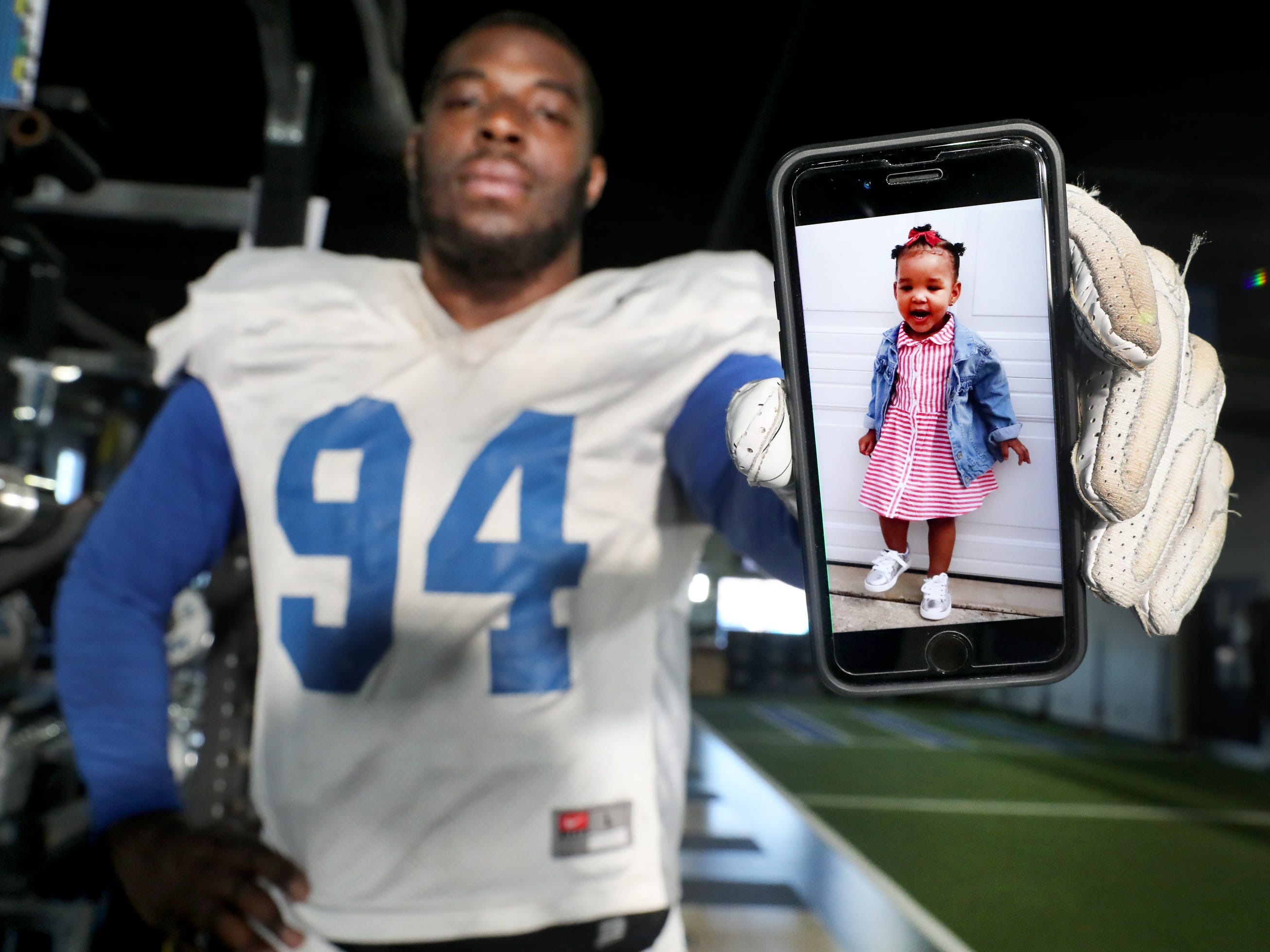 MTSU's defensive lineman Tyshun Render holds up a image of his one-year-old daughter Kenzlie Render, in the MTSU weight room, on Tuesday, March 26, 2019. Although Tyshun Render is currently practicing football for the upcoming fall season, part of his heart is back in Atlanta with his daughter Kenzlie Render, who he video chats daily.