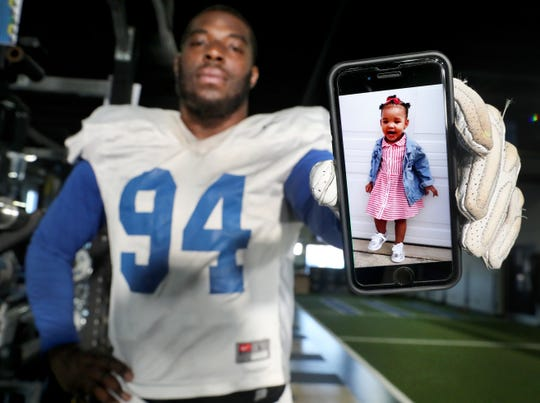 MTSU defensive lineman Tyshun Render holds up an image of his 1-year-old daughter Kenzlie, who lives three hours away near Atlanta.
