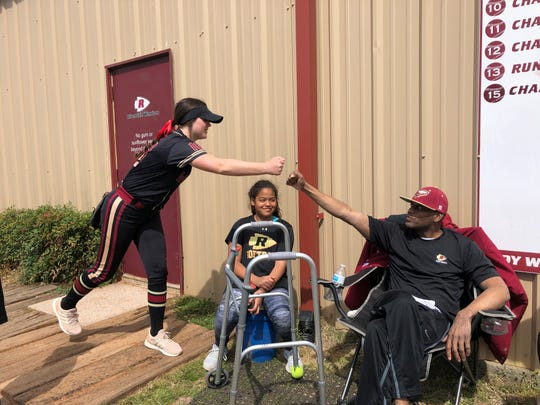 Riverdale assistant softball coach Perry Lyons fist-pumps Lady Warrior player Sydney Williams as Lyons' daughter, Gabi, looks on Saturday, March 23.