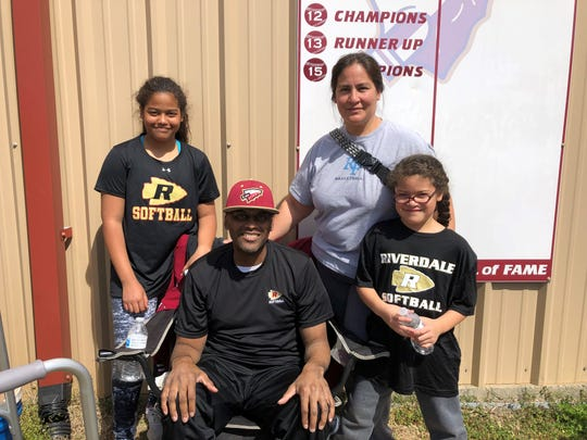 Riverdale assistant softball coach Perry Lyons (seated) is pictured with his wife, Sandy, and daughters Gabi (left) and Addy (right).