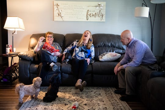Phyllis and Annemarie Rainwater (center) laugh as they feed their dogs snacks as Rick Rainwater, watches at their home Tuesday, March 26, 2019, in Shelbyville, Tenn. Rick and Phyllis adopted Annemarie when she was 17 after fostering her as a teenager.