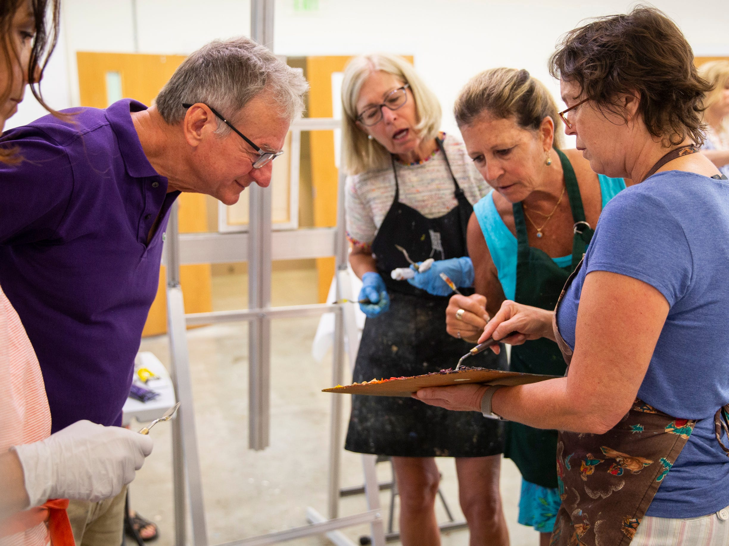 From left to right, Leonza Machielse, David Neden, Ann Fitzgerald, and Maryellen Shea watch as instructor Angela Anderson, right, shows them how to mix the correct colors for their painting during a palette knife painting class at the Naples Art Association in Naples on Wednesday, March 27, 2019.