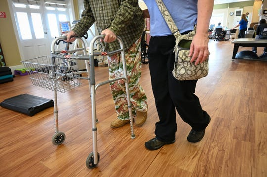 February 12, 2019 - St Petersburg, FL. Bon Secours Maria Manor Nursing Home. A physical therapy assistant works with a resident on his gate and balance.