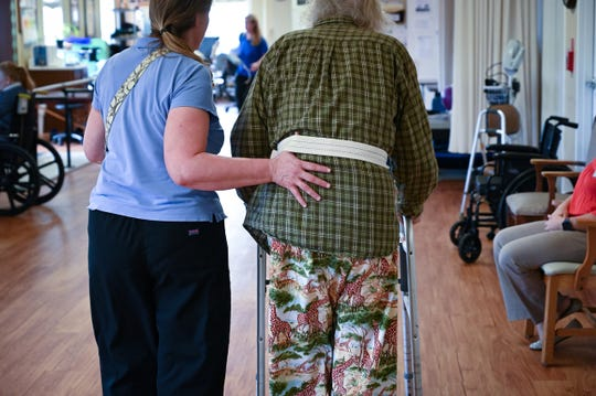 A physical therapy assistant works with a resident on his gate and balance at Bon Secours Maria Manor nursing home in St Petersburg, Fla., on Feb. 12, 2019. Bon Secours, which is a highly-rated nonprofit home, is expecting to receive almost $850,000 less per year under a new Medicaid payment plan signed into law in 2017.